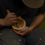 Carving a traditional wooden cup with an axe and knife
